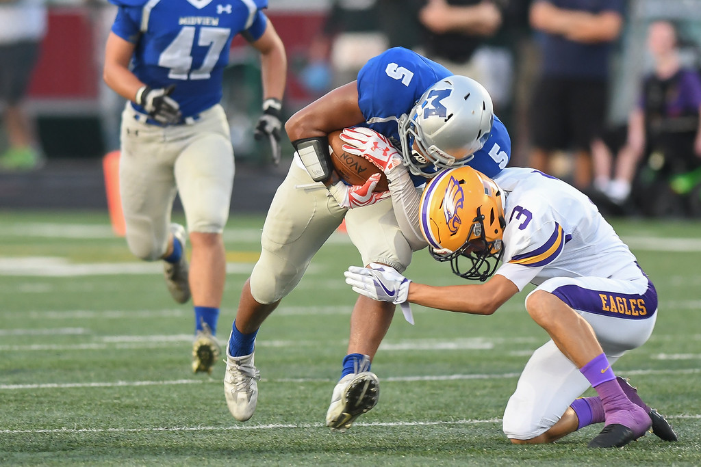 . Eric Bonzar�The Morning Journal Midview\'s Alonzo Banks (5) bangs helmets with Avon\'s Mitch Cooper (3), Sept. 16, 2016.