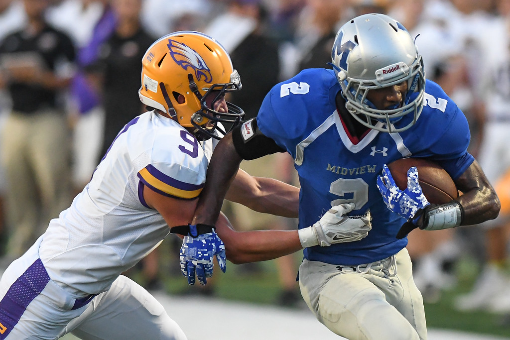 . Eric Bonzar�The Morning Journal Midview\'s Keith Johnson (2) fights for extra yards as he\'s wrapped up by Avon\'s David Orlando (9), Sept. 16, 2016.