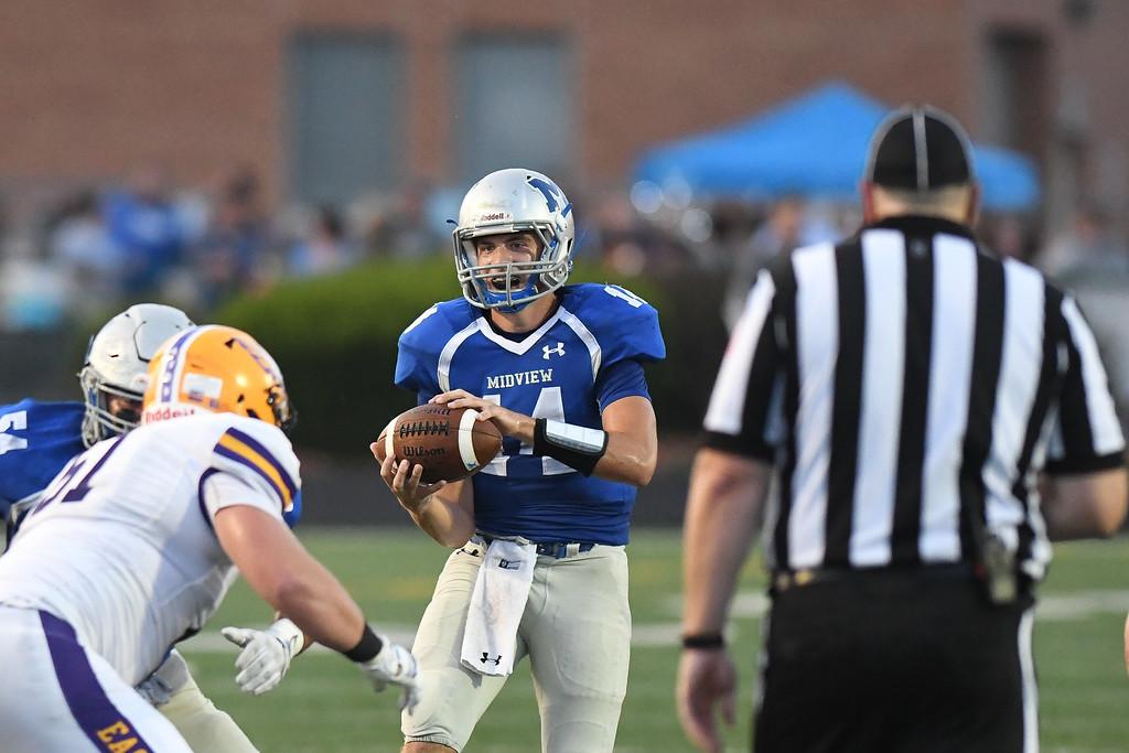 . Eric Bonzar�The Morning Journal Midview quarterback Dustin Crum (14) handles the snap, Sept. 16, 2016.