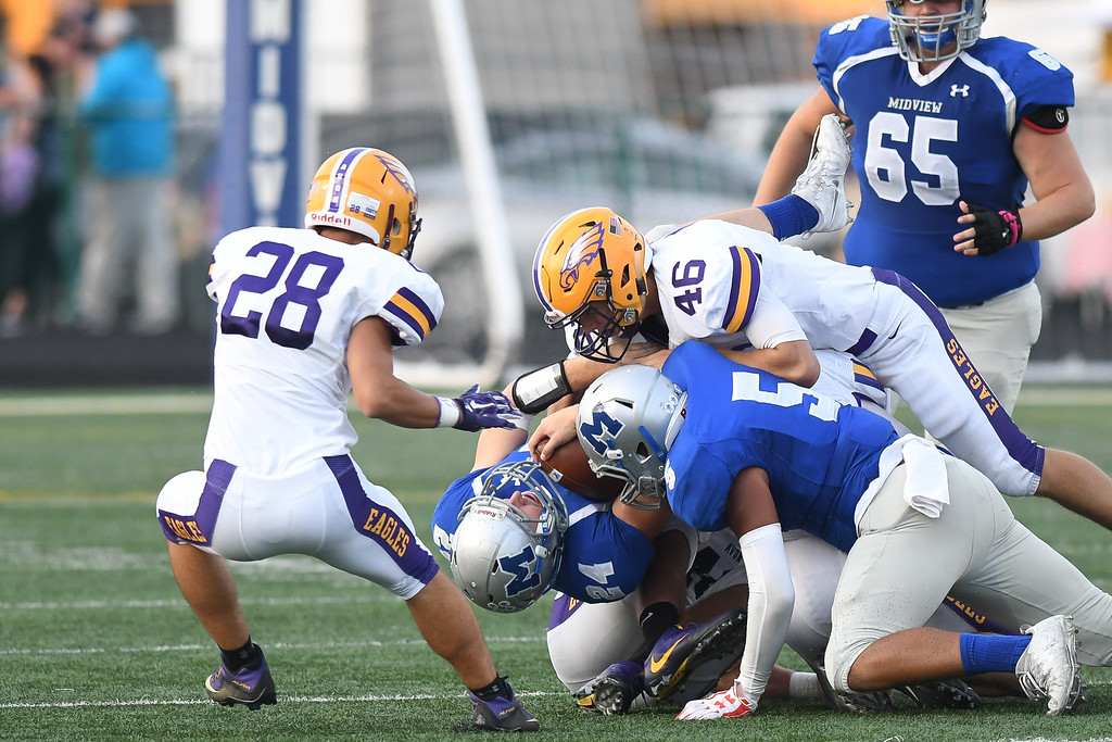 . Eric Bonzar�The Morning Journal Midview\'s Alec Forrer (24) is bent back by Avon defender Will Kocar (46), Sept. 16, 2016.