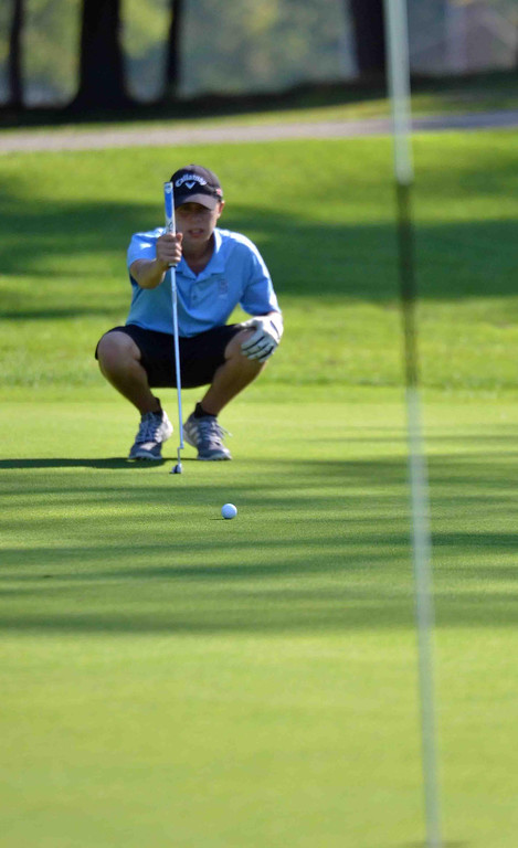 . Paul DiCicco - The News-Herald South Junior, Adam Paris, lines up his putt attempt from 30 feet away.