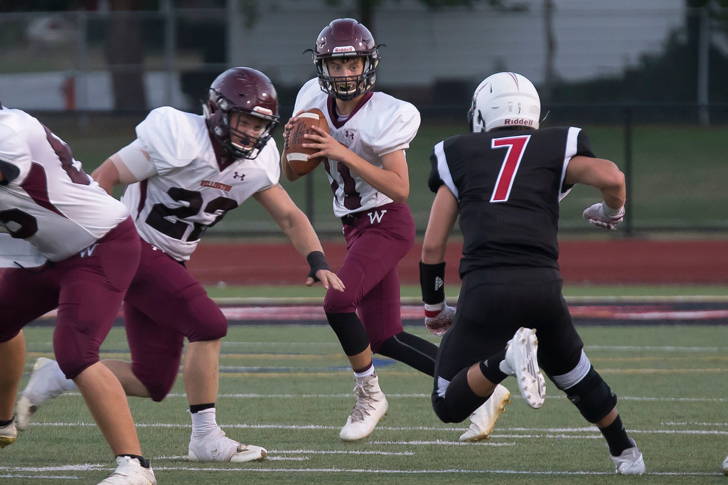 . Jen Forbus - The Morning Journal<br> Wellington quarterback Mason Wright looks for an open receiver while Justin Skinner (22) buys him time from Lutheran West\'s Jeremy Geye on Sept. 22.