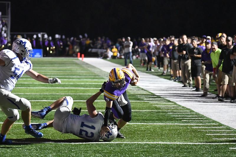 Eric Bonzar—The Morning Journal<br>Avon quarterback Ryan Maloy (5) tumbles his way past Midview defensive lineman Seth Frambach (12), Sept. 22, 2017.
