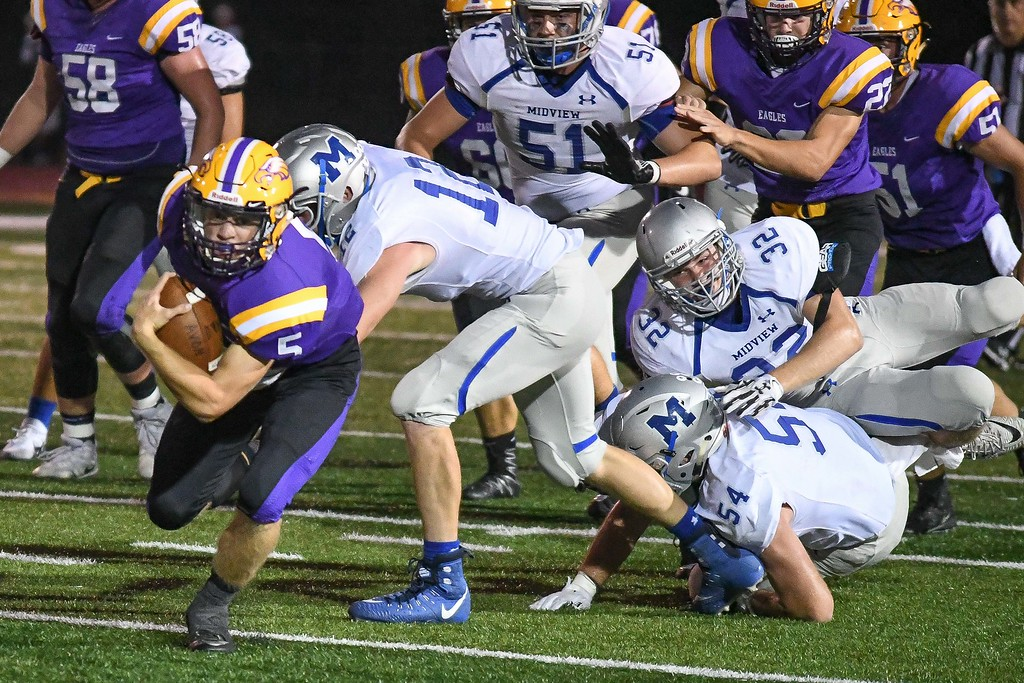 . Eric Bonzar�The Morning Journal<br> Avon quarterback Ryan Maloy (5) barrels his way past the Midview defensive line, Sept. 22, 2017.