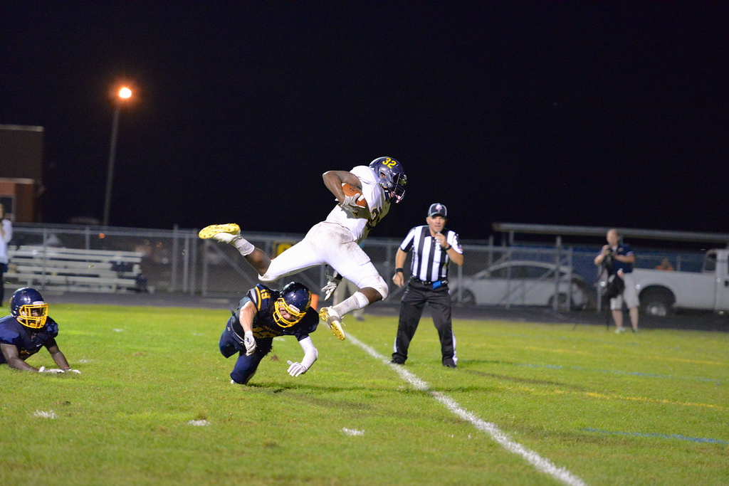 . Aimee Bielozer - The Morning Journal<br> North Ridgeville\'s Shomari Williams hurdles an Olmsted Falls defender for a touchdown on Sept. 22.