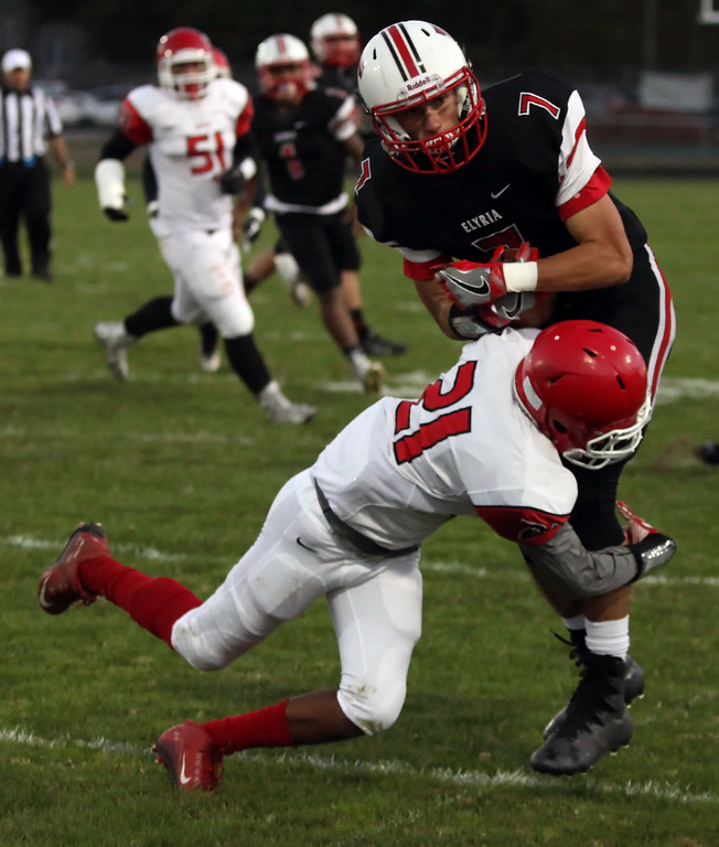 . Randy Meyers - The Morning Journal<br> Elyria\'s Jarrett Walker is brought down by Cameron Jones Jr. of Shaker Heights after making a first down catch during the first quarter on Sept. 28.