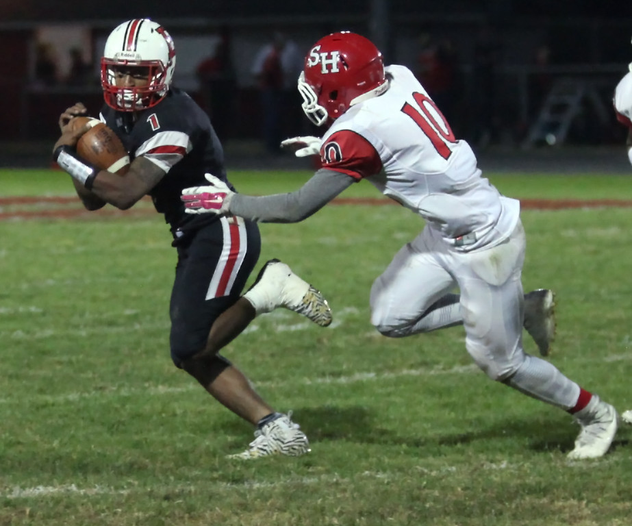 . Randy Meyers - The Morning Journal<br> Elyria quarterback Dontae Beckett scrambles away from the pressure applied by Shaker Heights\' Domontae Haywood during the second quarter on Sept. 28.