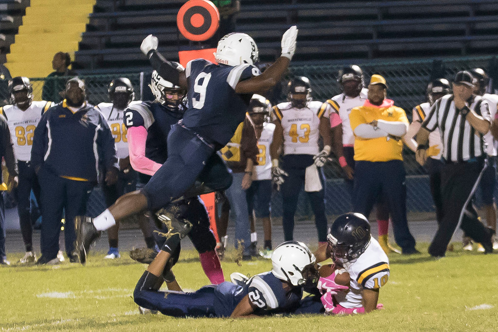 . Jen Forbus - The Morning Journal<br> In a graceful attempt to avoid teammate Zion Cross (22) and Warrensville Heights wide receiver Joshua Johnson (10), Lorain\'s Cairo Smith (9) leaps over the pile on Oct. 6.