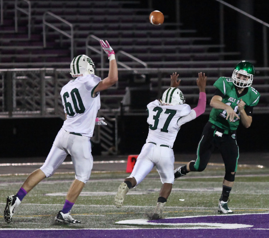 . Randy Meyers -- The Morning Journal Holy Name quarterback Joe Carter throws downfield and over the pass rush by Stephen Ferguson lll and Gabe Hirsch of Elyria Catholic.