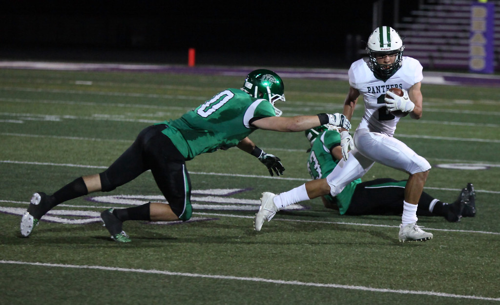 . Randy Meyers -- The Morning Journal Elyria Catholic\'s Donovan Warfield eludes two defensive players from Holy Name during a long gain during the second quarter.