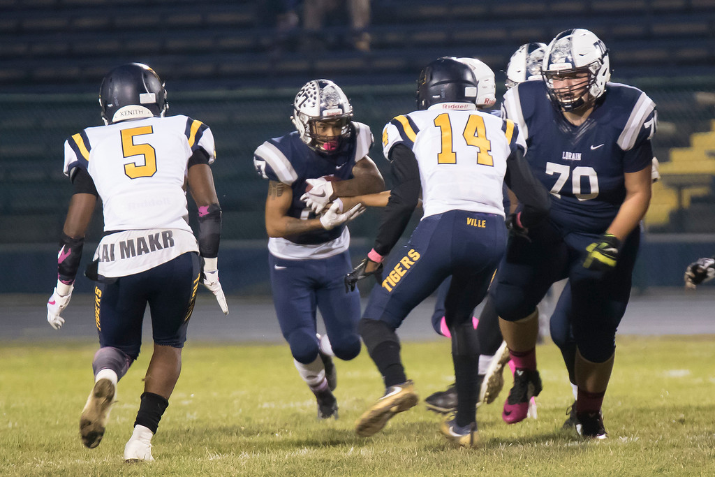 . Jen Forbus - The Morning Journal<br> Taking the handoff, Lorain running back Dakota Mincy (27) faces Warrensville Heights defender Nicholas Mcgee (14) on Oct. 6.