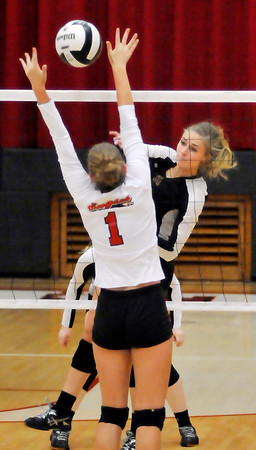 John P. Cleary | The Herald Bulletin<br /> Alexandria's Megan Miller hits the ball between Frankton's Anna Sperry hands to make a kill.