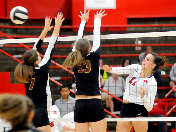 John P. Cleary | The Herald Bulletin<br /> Frankton's Ryann Shively hits the ball past the Alexandria defenders Blaine Kelly and Regan Lundy.