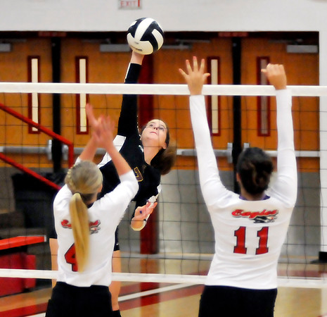 John P. Cleary | The Herald Bulletin<br /> Alexandria's Blaine Kelly goes for a kill as Frankton's Audrey Cleek and Ryann Shively defend.