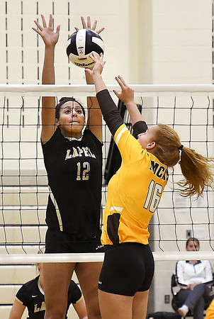 John P. Cleary | The Herald Bulletin<br /> Lapel's Makynlee Taylor goes up to defend the net as Monroe Central's Mikayla Fields taps the ball over the net.