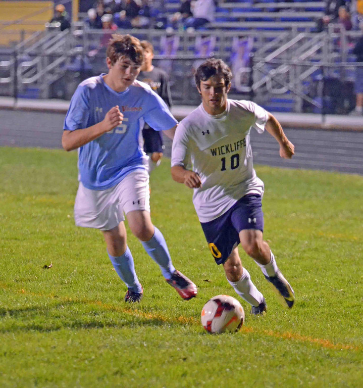 . Paul DiCicco - The News-Herald Wickliffe Junior, Nick Colbert, drives against a VASJ defender toward the goal on Oct 12.