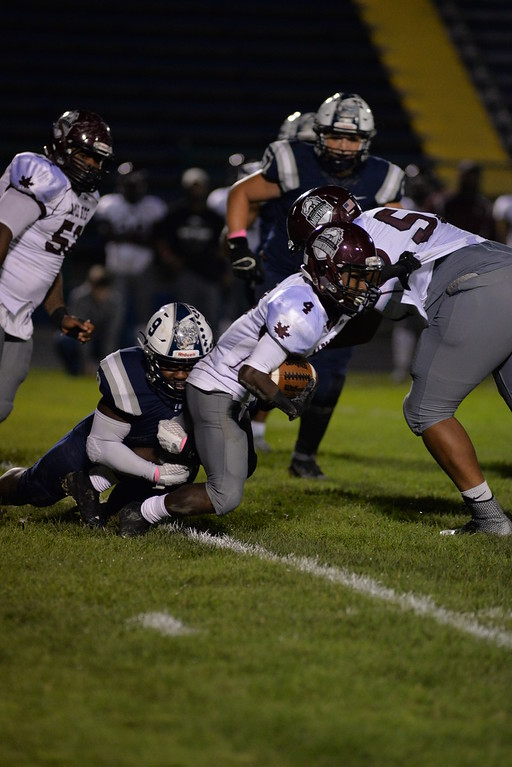 . Aimee Bielozer - The Morning Journal<br> Maple Heights\' Bernard bates gets tackled by Lorain\'s Cairo Smith on Oct. 13.