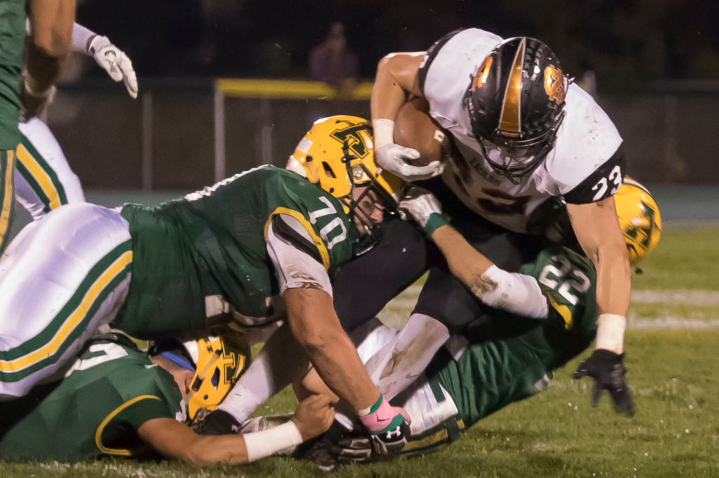 . Jen Forbus - The Morning Journal<br> Amherst\'s Matt Lee (70) and Hunter Parker (22) bring down North Olmsted running back Darren Anders on Oct. 13.