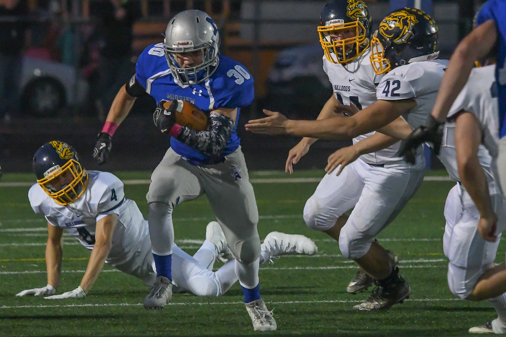. Eric Bonzar�The Morning Journal<br> Midview\'s Ben Gendics (30) breaks through the Olmsted Falls defensive line, Oct. 13, 2017.