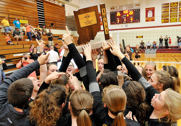 John P. Cleary |  The Herald Bulletin<br /> Alexandria players hoist the sectional championship trophy high after defeating Monroe Central in three sets.
