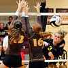John P. Cleary |  The Herald Bulletin<br /> Alexandria's Megan Miller hits the ball past the two Monroe Central defenders for a kill.