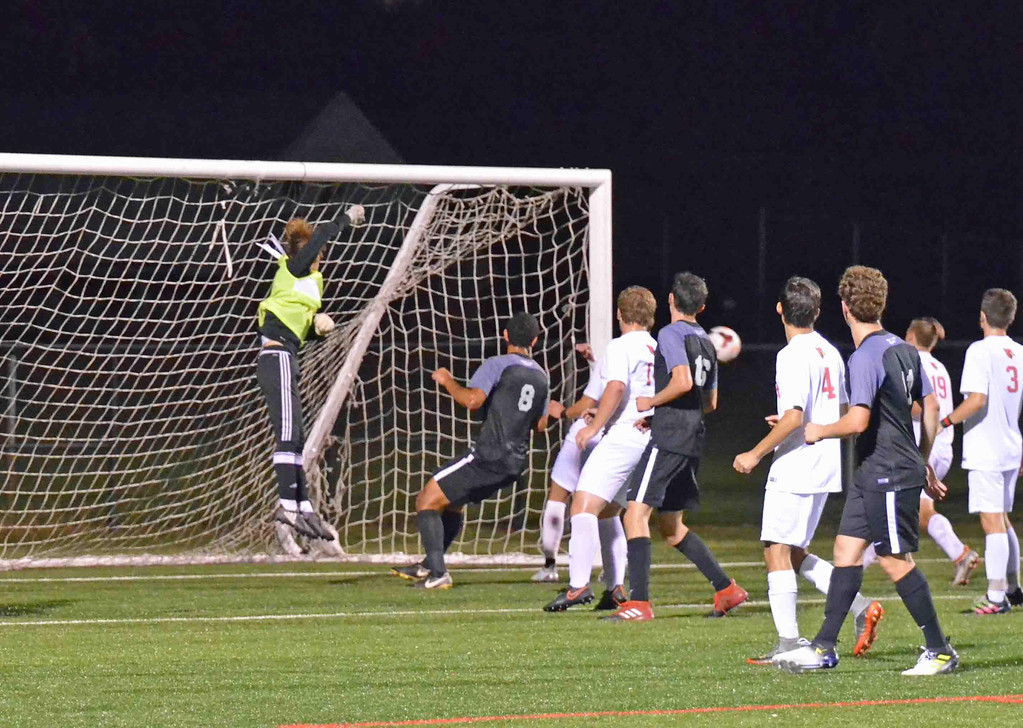 . Paul DiCicco - The News-Herald Mentor\'s goalkeeper punches the ball from the front of the net avoiding a charging George Nageeb (8) in a contest against University School on Oct 14.  Mentor went on to win 1-0.