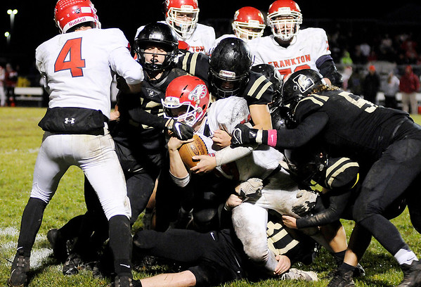 Don Knight | The Herald Bulletin Frankton's Landon Bouslog is tackled by a host of Bulldogs as Lapel hosted the Eagles in the first round of the sectional on Friday.
