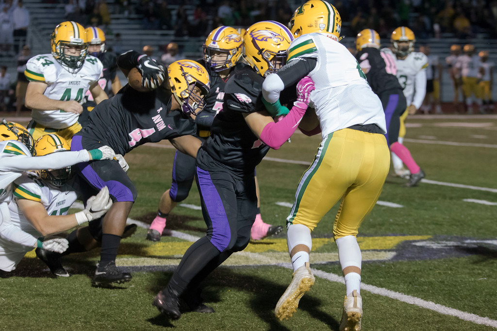 . Jen Forbus - The Morning Journal<br> Avon running back Tony Eberhardt (4) powers through the Amherst defense to gain yards on Oct. 20.