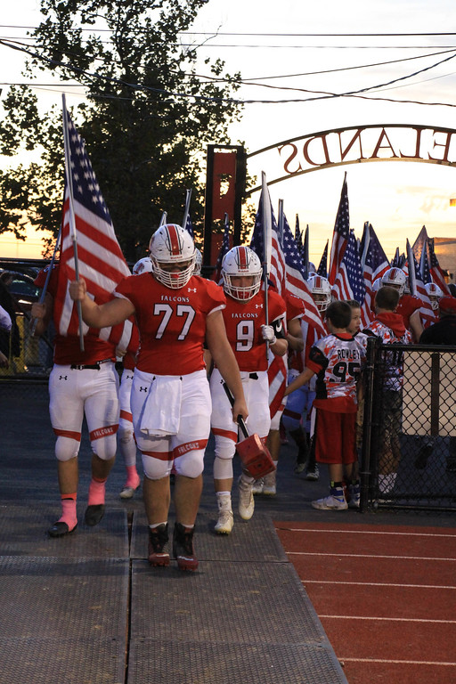 . Nicholas Pfeifer - The Morning Journal<br> Sean Lipscomb leads the Firelands Falcons to the field with flags in hand in support of Military Appreciation night on Oct. 20.