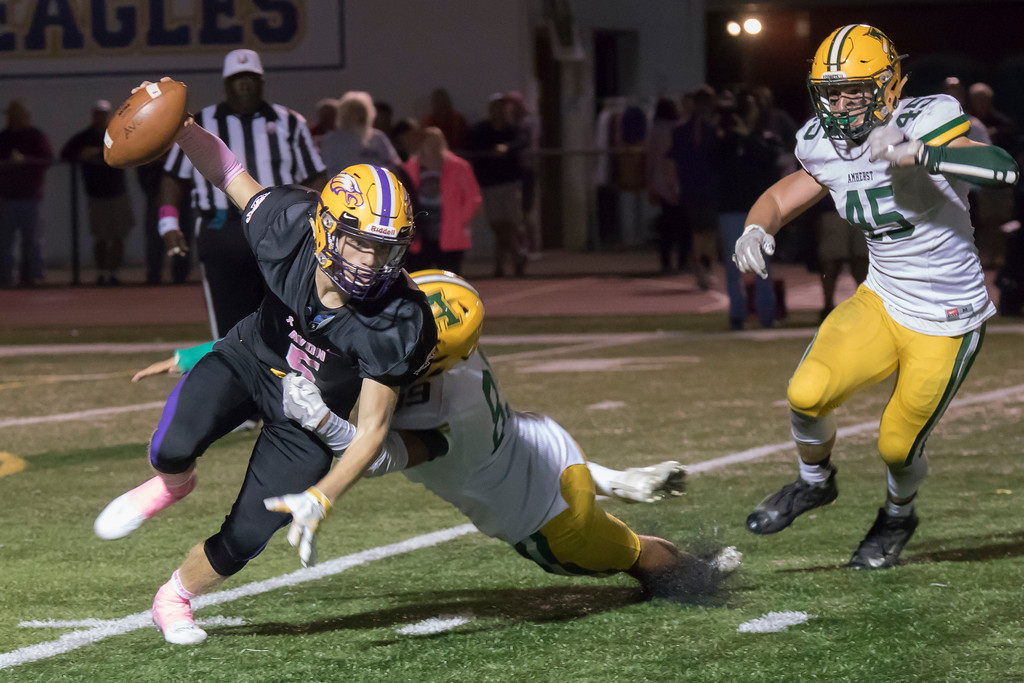 . Jen Forbus - The Morning Journal<br> Avon quarterback Ryan Maloy (5) struggles to stay on his feet as Amherst\'s Greg Rhodes (89) battles to bring him down on Oct. 20.