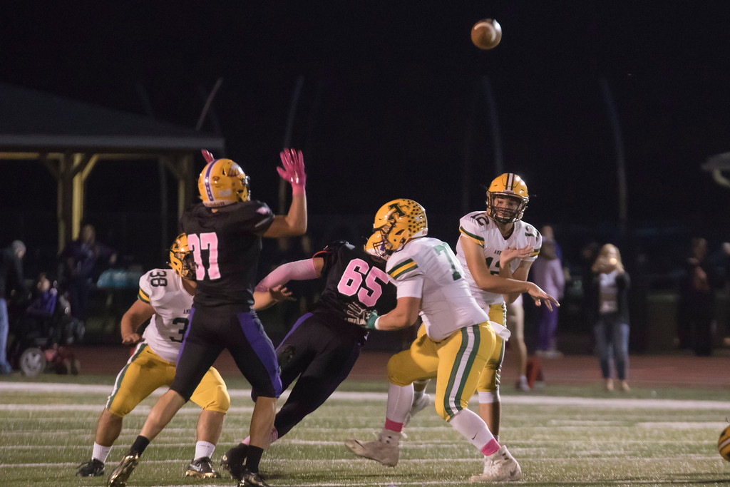. Jen Forbus - The Morning Journal<br> Amherst quarterback Matt Fairchild (12) finds an open receiver as running back Aaron Gonzalez (38) and center Matt Lee (70) provide him plenty of time against Avon on Oct. 20.