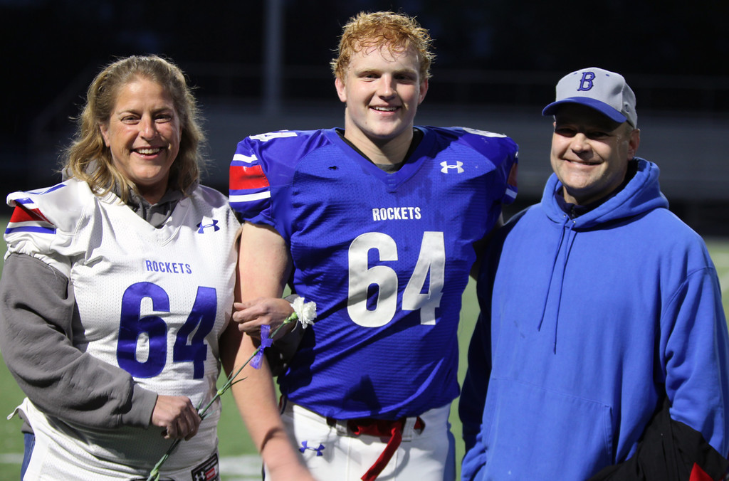 . Randy Meyers - The Morning Journal<br> Mike and Stacey Koss escort their son, Jonathan, onto the field for pregame introductions on senior night at Bay.