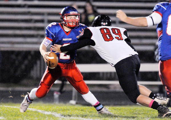 Don Knight | The Herald Bulletin<br /> Elwood quarterback Jake Wilson evades Blackford's Tyler Cagle before throwing a 63 yard touchdown pass in the sectional 36 semifinal on Friday.