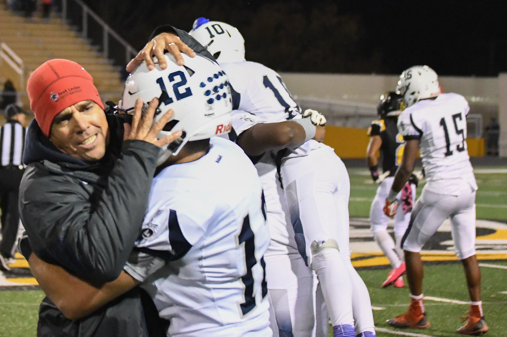 . Eric Bonzar�The Morning Journal Head Coach David McFarland hugs Brandin Sturgill after beating the Cleveland Heights Tigers, 14-13, and clinching their first Lake Erie League Conference championship in school history, Oct. 28, 2016.