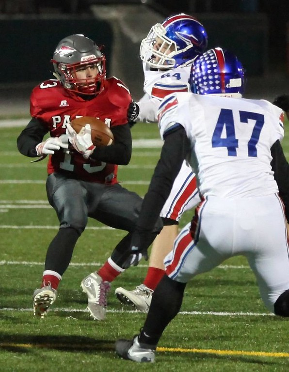 . Randy Meyers - The Morning Journal Parma running back Vinny Livdur is stopped by Thonas Koss and Sean Chambers of Bay after a short gain during the first quarter on Oct. 27.