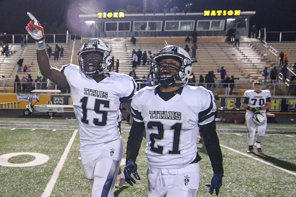 . Eric Bonzar�The Morning Journal Lorain Titans\' Naz Bohannon (15) and Zion Cross (21) celebrate after beating the Cleveland Heights Tigers, 14-13, and clinching their first Lake Erie League Conference championship in school history, Oct. 28, 2016.