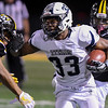 Eric Bonzar—The Morning Journal<br /> Lorain Titans running back Carlos Chavis (33) stiff arms his way past Cleveland Heights' Rahmon Davis-Smith, Oct. 28, 2016.