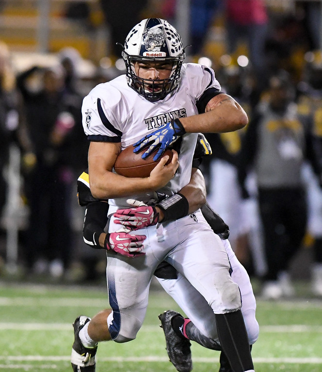 . Eric Bonzar�The Morning Journal Lorain Titans running back Aaron Huff (9) powers forward with Cleveland Heights\' Zaire Webb holding on, Oct. 28, 2016.