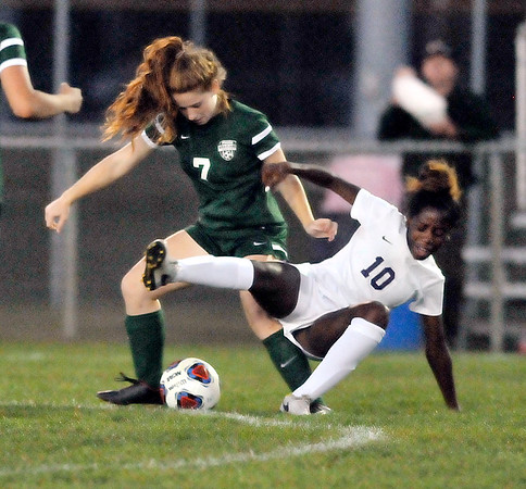 John P. Cleary |  The Herald Bulletin<br /> Muncie Central's Destiny Roberts trips as she fights for the ball with Pendleton's Sarah Dix.