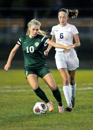 John P. Cleary    The Herald Bulletin<br /> Pendleton's Taylor Fort works the ball up field against Muncie Central's Gabby Merkel.