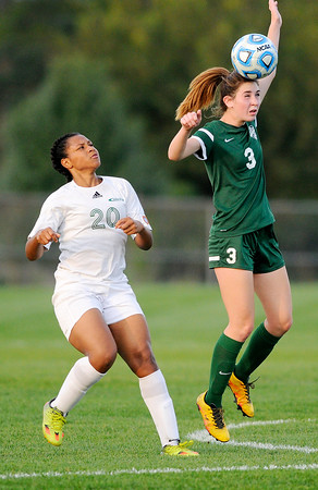 Don Knight | The Herald Bulletin<br /> Pendleton Heights' Kate Cowger heads the ball as Anderson's Alandis Hill looks on during the opening game of the girls soccer sectional at Noblesville on Tuesday.