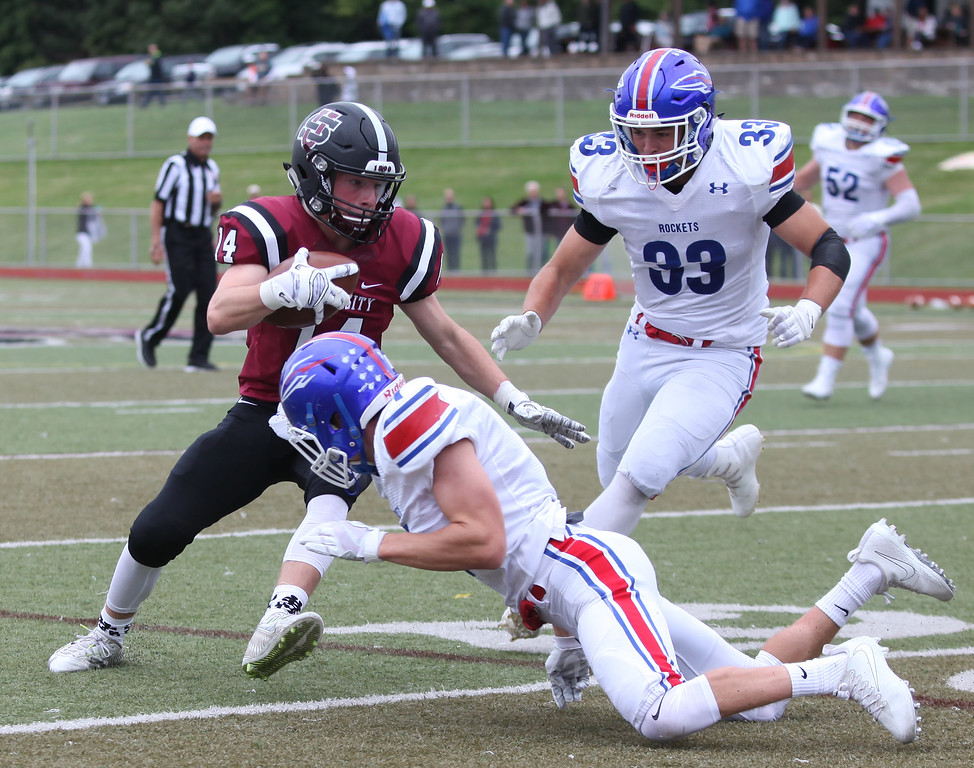 . Randy Meyers - The Morning Journal<br> University receiver Nic Pujolas is tackled after a gain by Nick Baerenstecher and Mark Olson of Bay during the second quarter on Sept. 2.
