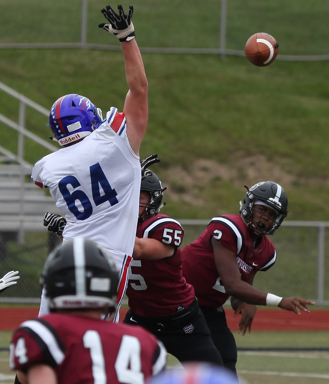 . Randy Meyers - The Morning Journal<br> University quarterback Jayden Cunningham throws around the pass rush by Thomas Koss of Bay during the first quarter on Sept. 2.