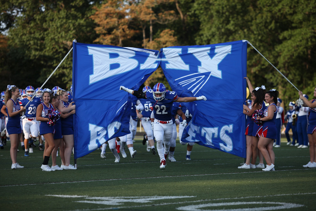 . Randy Meyers - The Morning Journal<br> Bay senior Trey Psota leads the Rockets onto the field for the opening game against Keystone on Aug. 25.