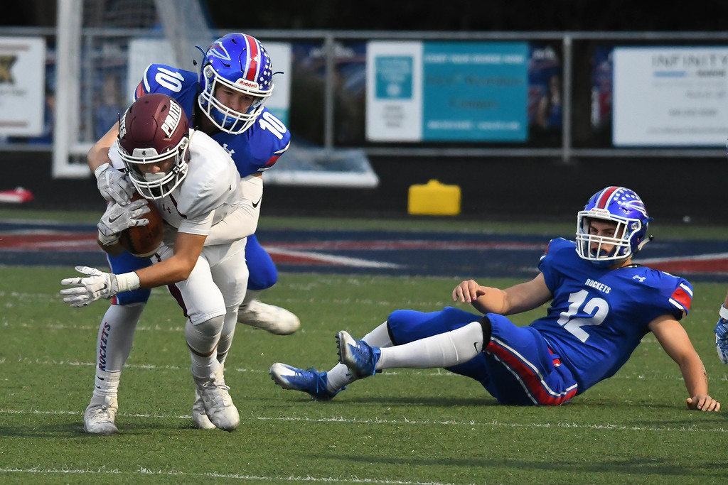 . Eric Bonzar�The Morning Journal <br>  Rocky River\'s Cameron Blue (4) is wrapped up from behind by Bay defender Dillon Barry (10), Sept. 29, 2017.