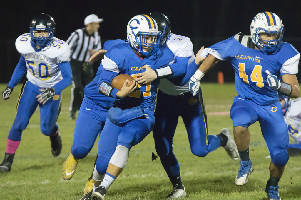 . Jen Forbus - The Morning Journal<br> Clearview running back Drew Engle (21) hangs on to teammate David Renftle (44) as Brooklyn linebacker Matt Crossman tries to move in for a tackle on Oct. 27.