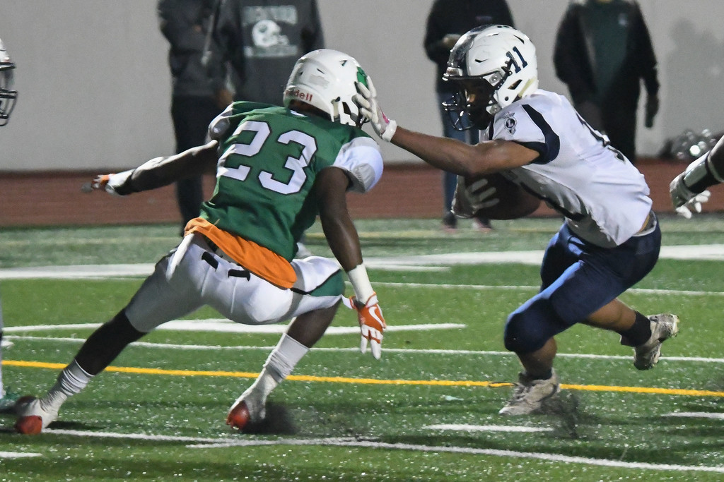. Eric Bonzar�The Morning Journal<br> Titans running back Daylin Dower(11) stiff arms his way past Bedford\'s Dionte Clemis (23), Oct. 20, 2017.