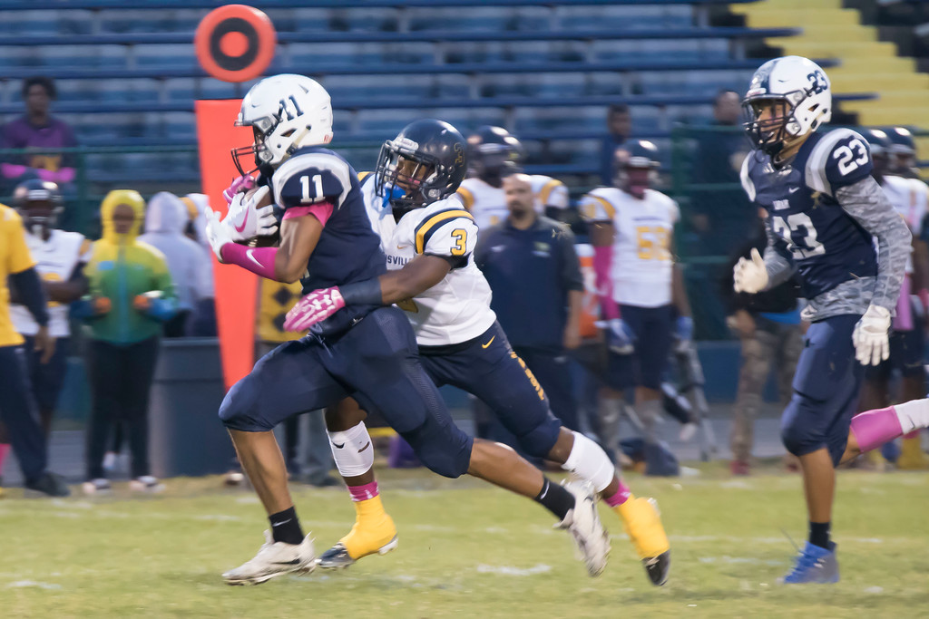. Jen Forbus - The Morning Journal<br> Lorain running back Daylin Dower (11) protects the football as Warrensville Heights strong safety Jaleel Paterson (3) closes in on Oct. 6.