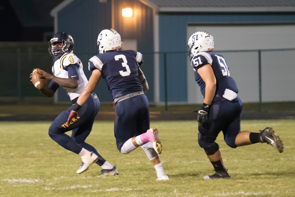 . Jen Forbus - The Morning Journal<br> Warrensville Heights quarterback Devyn Byers looks for a receiver as Lorain\'s defensive end Nate Melendez (3) and linebacker Kelvin Torres (51) close in on Oct. 6.