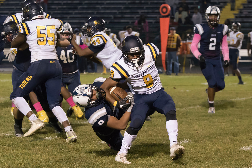 . Jen Forbus - The Morning Journal<br> Lorain defensive Malik McCall (8) hangs on in an attempt to bring down Warrensville Heights quarterback Jerome Lee (9) on Oct. 6.